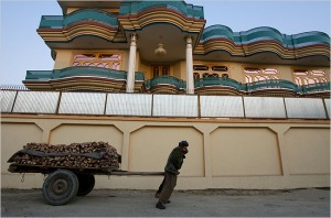 A man pulls a cart loaded with fire wood past a mansion owned by high-ranking government officials in the Sherpur neighborhood of Kabul. (Danfung Dennis for The New York Times)