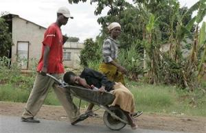 A woman suffering from the symptoms of cholera is taken in a wheelbarrow to a clinic in Harare December 12, 2008. REUTERS/Philimon Bulawayo